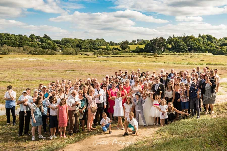 Photos de groupe des mariés et de tous les invités en extérieur