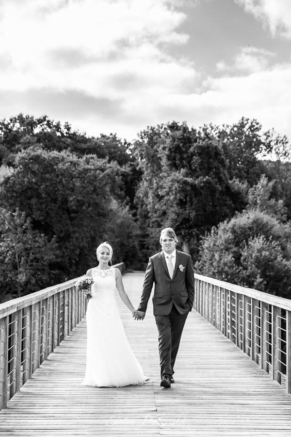 Photo de couple des mariés, main dans la main, sur un pont