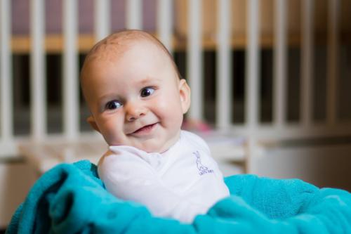 Photographie de bébé, assis dans un panier avec le sourire