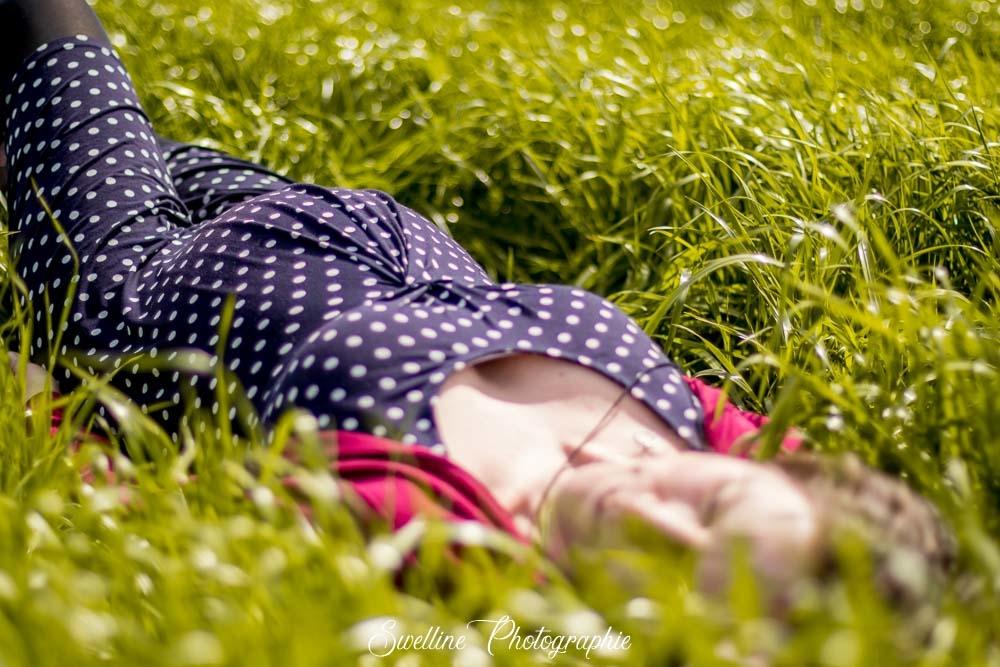 Photographie de grossesse, future maman allongée dans l'herbe