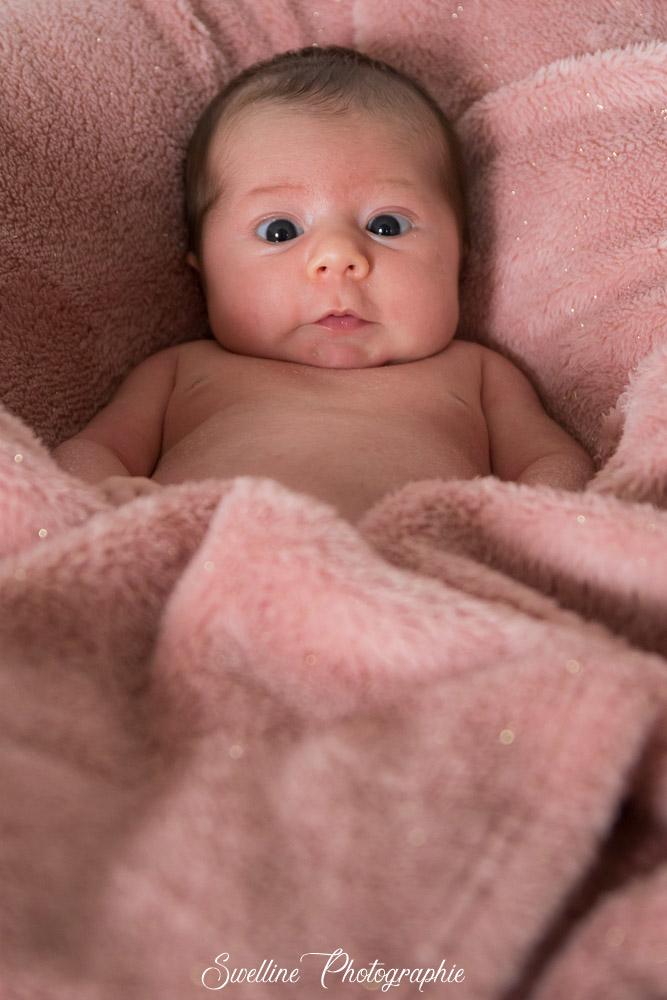 Photographie bébé qui louche dans les couvertures