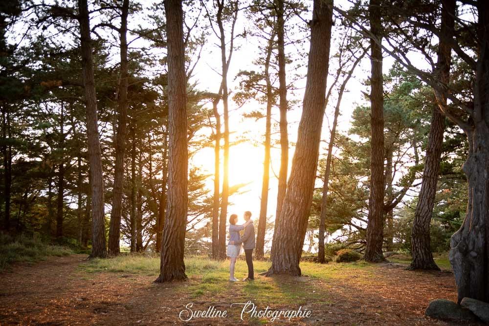 Photographie de grossesse en couple dans le soleil couchant