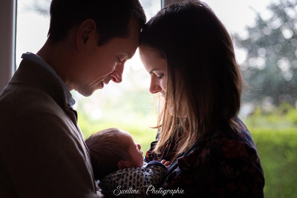Photographie de bébé avec ses parents à la maison