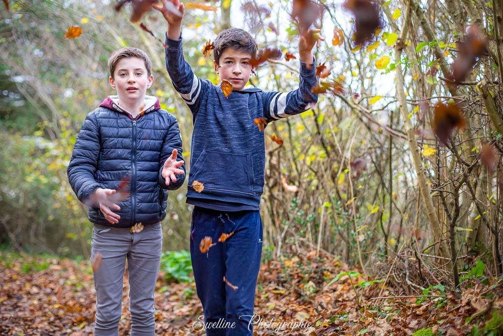 Photographie d'enfants s'amusant avec les feuilles
