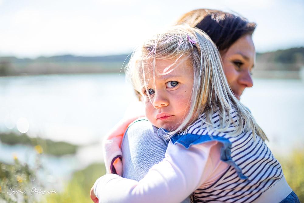 Photographie de famille, petite fille dans les bras de sa maman