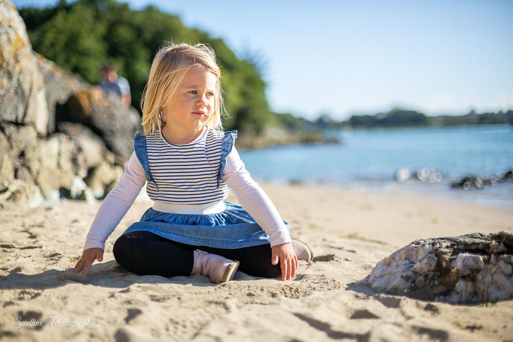 Photographie petite fille assise dans le sable