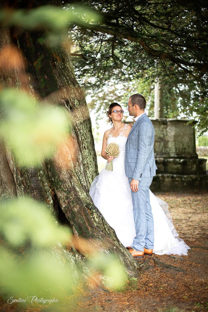Photo de couple des mariés au pied d'un arbre