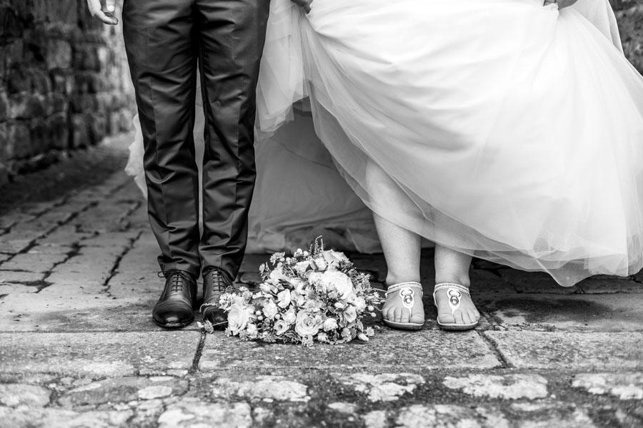 Les pieds et le bouquet des mariés