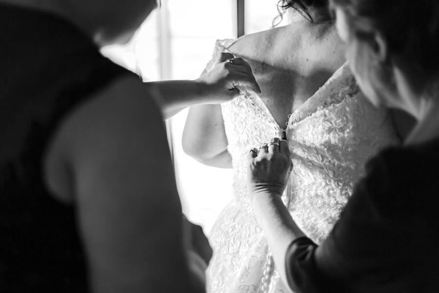Préparatifs et habillage des mariés, boutonnage de la robe